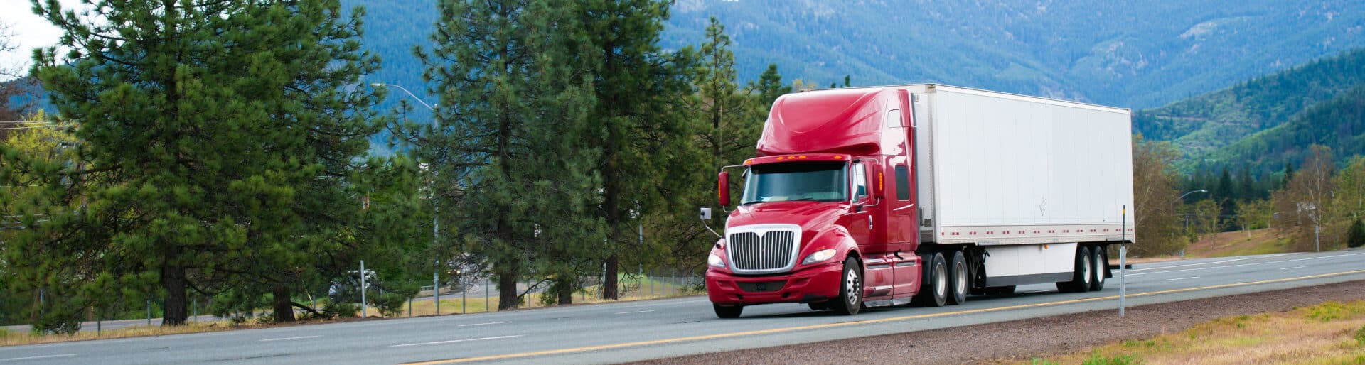 Red big rig modern shiny semi-truck with white dry van trailer with aerodynamic skirt move on straight