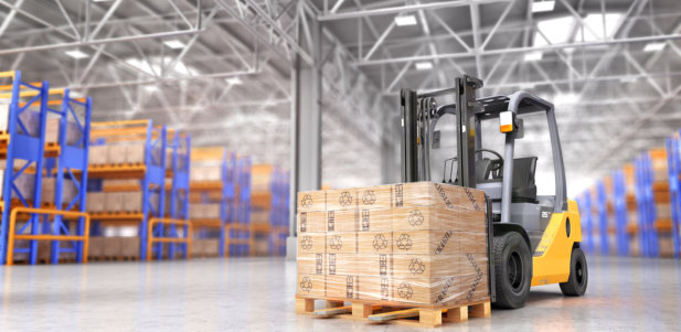 The forklift in the big warehouse on blurred background